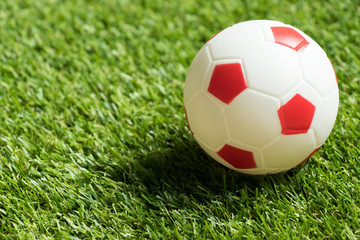 Toy red and white color football on artificial green grass background