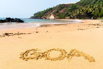 inscription on the sand. The inscription Goa on a sandy beach against the blue sea and the turquoise water and waves