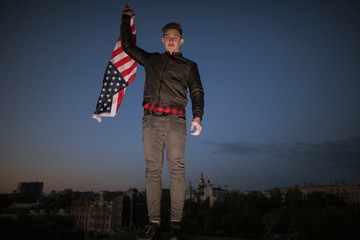 Guy with US flying flag at night city. Proud american patriot celebrate national event. Teenager on vacation have fun at the independence day