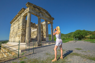 Travel woman photographer with professional camera takes shot of Mausoleum, Historical Site of Ancient Messene, Peloponnese, Greece. Seductive female photographing a Greek Temple. Europe summer travel