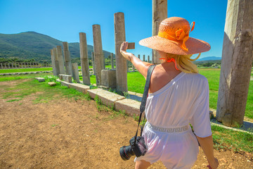 Travel photographer takes picture with her smart phone at columns of Ancient Messene Historical Site in Peloponnese, Greece. Seductive female in greek dress photographing the ruins. Holidays lifestyle