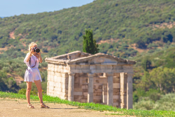 Travel woman photographer in greek dress takes shot of Archaeological Site of Ancient Messene, Peloponnese, Greece. Seductive female photographing a Greek Temple. The Mausoleum on blurred backgroung.
