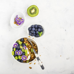 Healthy Breakfast: homemade roasted granola with blueberries, kiwi fruit and edible flowers on wooden background. From the top view. The concept of fitness nutrition
