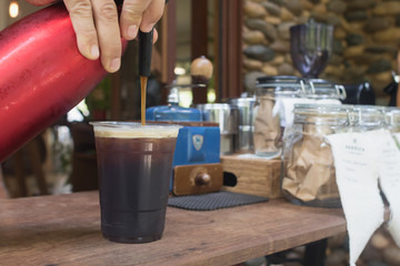 Barista is  forcing nitrogen into the the coffee.Sparkling Nitro Cold Brew Coffee on wood table outdoor coffee cafe