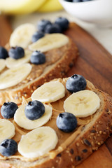 Banana, blueberries and peanut butter on wholemeal bread - shallow dof