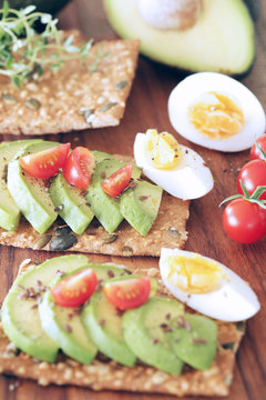 Avocado, boiled egg and tomato on pumpkin seeded crackers - shallow dof