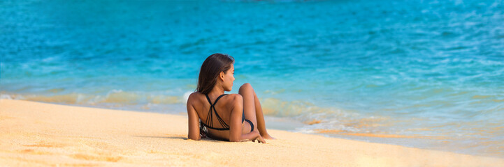 Wall Mural - Beach relaxation woman lying down on sand banner. Tropical vacation travel lifestyle bikini mellow girl. Holiday woman relaxing enjoying sun on holidays.