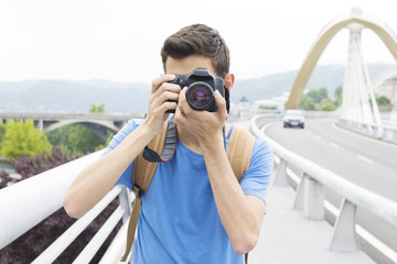 young man with the camera taking pictures in the city