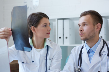 Male and female doctors discussing x-ray image.