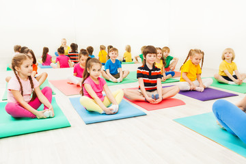 Kids doing butterfly exercise sitting on yoga mats