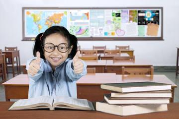 Cute schoolgirl showing ok sign in classroom