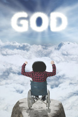 Disabled man with GOD text on sky