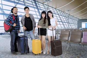 Diverse tourists standing with suitcases at the airport
