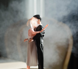 Doll wedding couple indoors is hugging each other. Beautiful model girl in white dress. Man in suit. Wedding love concept. Close up.