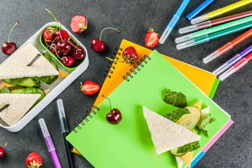 Back to school. A hearty healthy school lunch in a box: sandwiches with vegetables and cheese, berries and fruits (apples) with notebooks, colored pens on a black table. Copy space