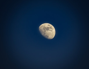 Gibbous moon over dark blue sky seen with a telescope at night. Picture with vignetting.