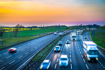 Colourful sunset at M1 motorway near Flitwick junction with blurry cars in United Kingdom. Fotomurales