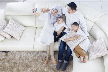 Muslim family taking selfie photo on sofa