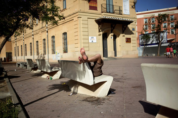 A man enjoys the sunny weather as he rests on a bench during the warmest weekend of the year so far, in Malaga