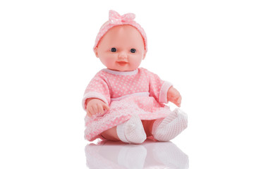 Cute little plastic baby doll with blue eyes sitting  isolated on white background