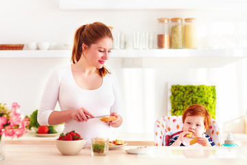 young mother and infant baby in high chair having breakfast in the kitchen