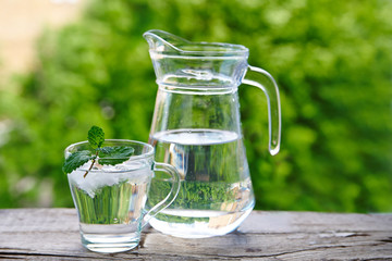 Glass cup with ice water  and mint, a jug of water on a wooden table against a background of green foliage