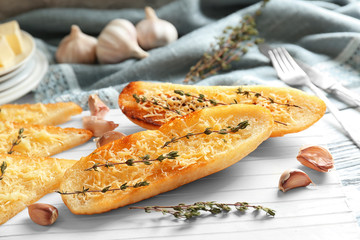 Tasty bread slices with grated cheese, garlic and herb on cutting board