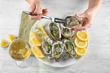 Woman eating tasty fresh oysters with sliced lemon and rosemary on plate. Aphrodisiac food for increasing sexual desire