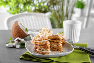 Stack of delicious coconut pancakes with butter cream, sweet sauce and shavings on table