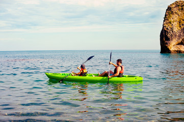 Man and boy swims on kayak in the sea on background of island. Kayaking concept