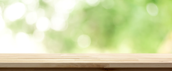 Wood table top on  blur abstract natural green background, panoramic banner