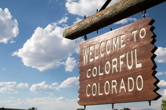 Welcome to Colorful Colorado sign against puffy clouds