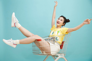 The young girl is in the shopping cart.