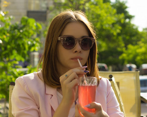 Young pretty girl drinks a cold beverage, outdoor