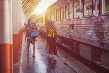 girl and a boy travelling with backpacks at a train station