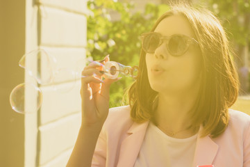 Young pretty girl blows bubbles, outdoor