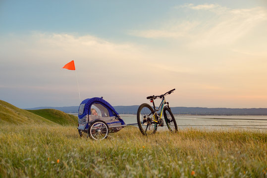 Biking in the hills at sunset with child trailer