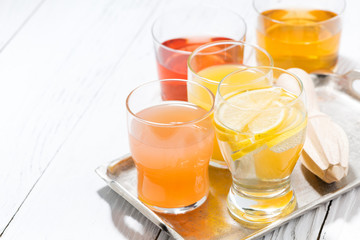 assortment of fresh citrus juices in glasses and white background