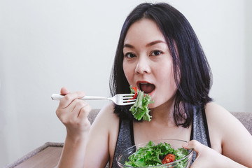 Fit healthy woman eating a fresh salad