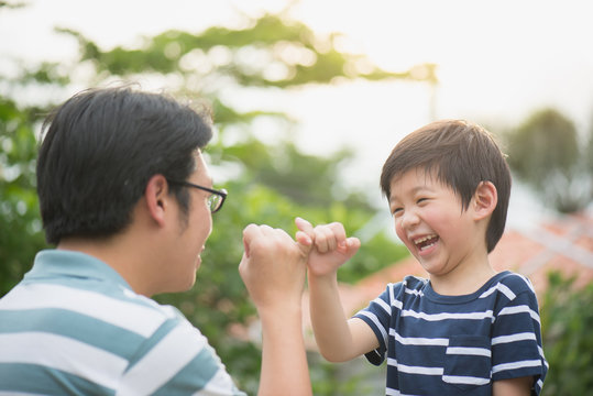 Asian father and his son making a pinkie promise