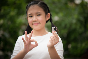 asian girl holding hearing aid