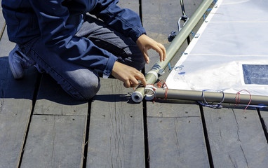 aspiring sailor prepares the sail of his boat the sailing course.