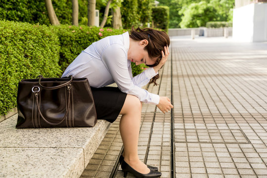 depressed business woman sitting on the bench.
