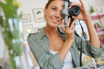Portrait of girl using camera in coffee shop
