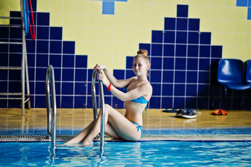 Portrait of a fabulous young girl in a blue swimsuit sitting at a pool in the water park.