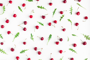 Cherry pattern. Fresh sweet cherry and arugula leaves on white background. Flat lay, top view