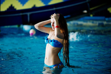 Portrait of an attractive young girl standing and posing in the pool wearing blue bikini in the water park.