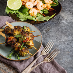 Mini barbecue with tuna and shrimp on a wooden skewer, grill, bbq. Simple background. Healthy food. Lifestyle.
