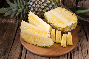 Ripe pineapple and pineapple slices on a wooden background tropical fruits