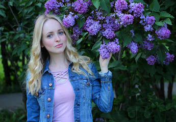 Young beautiful girl close-up stands on a background of beautiful and fragrant lilac